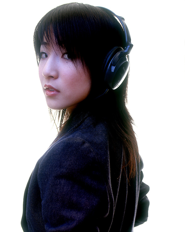 Studio Portrait of a Japanese female with headphones looking back