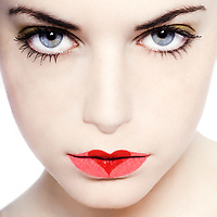 young beautiful caucasian woman playing with heart drawing on lips