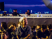 05 DECEMBER 2016 - BANGKOK, THAILAND:  A woman in a wheelchair waits for a ceremony honoring the late King of Thailand to start on Bhumibol Bridge. Tens of thousands of Thais gathered on Bhumibol Bridge in Bangkok Monday to mourn the death of Bhumibol Adulyadej, the Late King of Thailand. The King died on Oct 13 after a lengthy hospitalization. December 5 is his birthday and a national holiday in Thailand. The bridge is named after the late King, who authorized its construction. 999 Buddhist monks participated in a special merit making ceremony on the bridge.      PHOTO BY JACK KURTZ