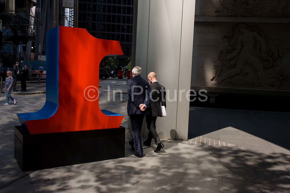 City workers pass-by a large number One, part of an art installation entitled 'One Through Zero (The Ten Numbers)' by American pop artist Robert Indiana (b 1928), in Lime Street, City of London, the capital's Square Mile, and its financial heart. Situated in the capital's Square Mile, its financial heart, are surrounding offices and corporate headquarters from the finance and insurance sector, most notably being the nearby Lloyds of London building. This series of sculptures is composed of 10 brightly painted numerical digits, each made of aluminum and set on its own base. Their construction took place at the former Lippincott Foundry in North Haven, Connecticut from 1980 to 1983