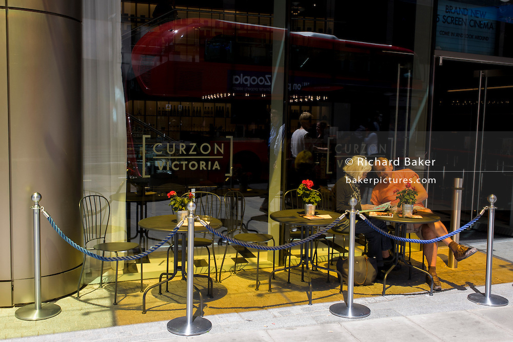 Orange-clothed man sits at cafe table, under orange glass in bright sunshine in central London.