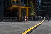 Two visitors to London walk through Leadenhall in the City of London, aka The Square Mile the capitals financial district, on 2nd September 2019, in London, England.