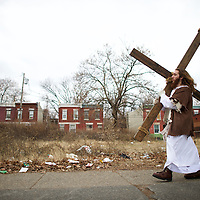 """Michael Grant, 28, """"Philly Jesus,"""" carries a 12 foot cross 8 miles through this blighted area of North Philadelphia towards LOVE Park in Center City as part of a Christmas walk to spread the true message of the holiday in Philadelphia, PA on December 20, 2014.   As many as a half dozen others joined him for numerous miles as he trekked southward down Broad Street.  Some shouted """"Praise Jesus!"""" and """"Thank you for doing this!""""at the sight.  Nearly everyday for the last 8 months, Grant has dressed as Jesus Christ, and walked the streets of Philadelphia to share the Christian gospel by example.  He quickly acquired the nickname of """"Philly Jesus,"""" which he has gone by ever since."""