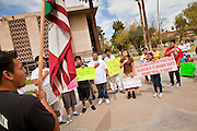 "14 MARCH 2011 - PHOENIX, AZ: Public school students say the ""Pledge of Allegiance"" during an immigrants' rights protest at the Arizona State Capitol in Phoenix Monday. Protests by immigrants' rights activists have continued as the state's conservative Republican legislators debate toughening the state's anti-immigrant bills. Some of the bills the state legislature has debated this year include eliminating birthright citizenship, a law that would require hospitals to check the immigration status of patients checking in for elective care, a bill that would require schools to verify the immigration status of students when they enroll and a bill that would require law enforcement to impound the cars of undocumented immigrants even if they have a legal driver's license from another state.      Photo by Jack Kurtz"