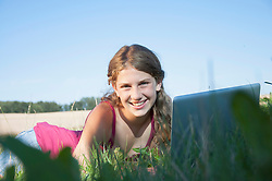 Girl (12-13) in meadow using laptop