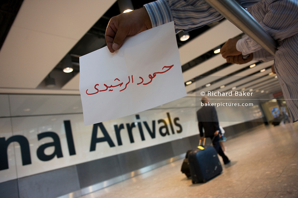 An unseen person holds out name card and awaits the arrival of a fellow-Kuwaiti on the ground floor of at Heathrow airport's T5