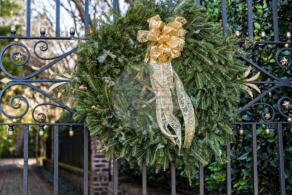 The wrought iron gate of a historic home decorated with a Christmas wreath on the Battery in Charleston, SC.