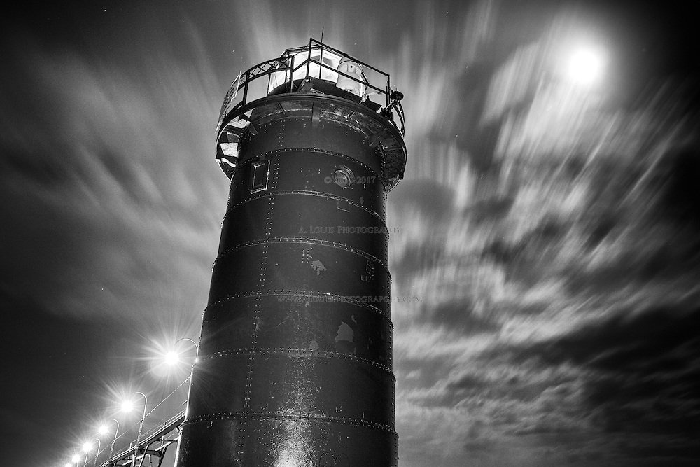 Long exposure of the full moon and clouds streaking past the lighthouse in South Haven