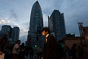 A Japanese salaryman, wearing a face mask, walks in front of the distinctive Cocoon Tower in Shinjuku, Tokyo, Japan. Friday September 14th 2018