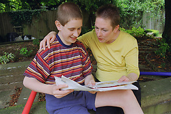 Mother reading outside with teenage son with autism,