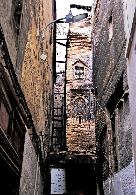 Ancient alley in the oldest part of the medina of Fes.  Multistorey brick tower projects from one building, while a hand written sign below offers building expertise.  Modern street lamp  is wired to an adjoining building, hardly less decrepit.