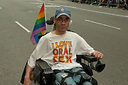 """Disabled participant in the 2011 Pride Parade in New York, wearing a tee short reading """"I Love Oral Sex."""""""