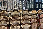 Nederland, Amsterdam, 7-5-2020 Per 1 juni mogen de cafes en andere horeca weer open en bedienen op terrassen voor 30 mensen en met anderhalve meter tussenruimte . De horeca is al enkele weken gesloten vanwege de coronadreiging maar de regering laat het normale dagelijks leven weer langzaam opstarten . Opgestapelde stoelen op de wallen in de binnenstad van Amsterdam . Unlock,beperkende,beperkingen, opheffen,versoepelen,versoepeling , opengooien. Foto: Flip Franssen