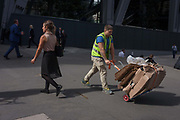 A workman pushes cardboard on a small trolley destined for recycling in Leadenhall Street, on 12th September, in the City of London, UK. All businesses in the City have a legal responsibility to ensure that they produce, store, transport and dispose of your business waste without harming the environment. This is called your Duty of Care DoC.