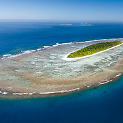 This is an aerial panorama of Taula Island in the Vava'u island group of the Kingdom of Tonga. The smaller island immediately behind and to the right of Taula is Lua Lole island. Further ub the background is the main island group. From this perspective, the considerable extent of the coral reef and sand associated with the island is clearly visible.