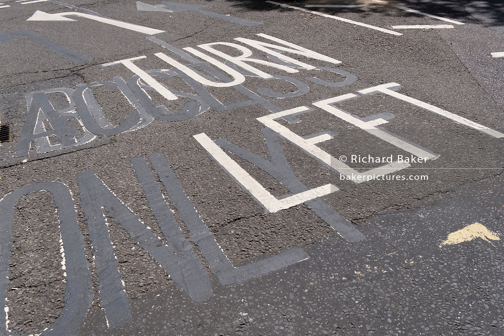 An urban landscape of road markings and the ghosts of previous versions, of the words 'Turn' Left', are seen from an elevated angle, in the road at Aldwych, on 23rd June 2021, in Westminster, London, England.