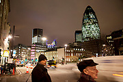 Night time scene in the City of London. People make their way home after work. Waiting to cross the street near to the iconic Gerkhin building