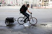 In San Francisco rijdt een fietser met aanhanger door het centrum. De Amerikaanse stad San Francisco aan de westkust is een van de grootste steden in Amerika en kenmerkt zich door de steile heuvels in de stad. <br /> <br /> A cyclist in San Francisco. The US city of San Francisco on the west coast is one of the largest cities in America and is characterized by the steep hills in the city.