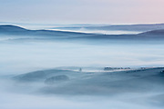 Captured from Mam Tor, this view towards a distant Abney Moor, overlooks a mist-covered Castleton and Cave Dale. Heavy frost and a temperature inversion - all the ingredients you need for a stunning winter's morning in the Peak District. January. Derbyshire, England, UK.