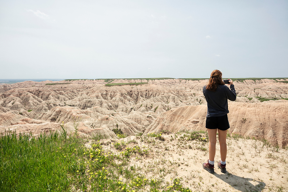 Young woman taking. a photo with her cell phone at Badlands National Park