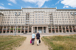 Two women walking towards historic socialist former East German apartment buildings on Karl Marx Allee in Berlin Germany
