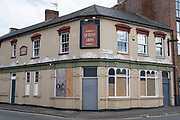 Closed down boarded up pub building in Deritend area near the city centre on 3rd August 2020 in Birmingham, United Kingdom. Due to the recession which started during the coronavirus pandemic, and the redevelopment of the area, many pubs have had to close, like the Queens Arms. Pubs have been particulalry hit hard during the recession with many established public houses closing every week.