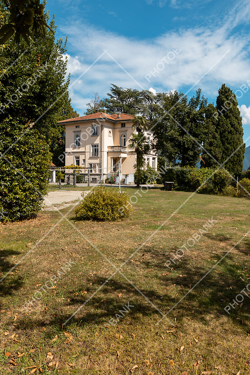 Large and old villa with large garden around it on a sunny summer day
