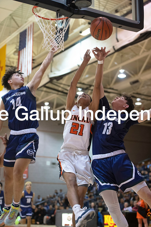 Gallup's Jeffrey Yazzie (21) is fouled by Rio Rancho's Christian Lucero (13) as he attempts a basket at Gallup High School Tuesday night in Gallup.