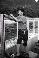 Chinese man sailing a boat with his foot on the river Li. Yangshuo, guanxi, china