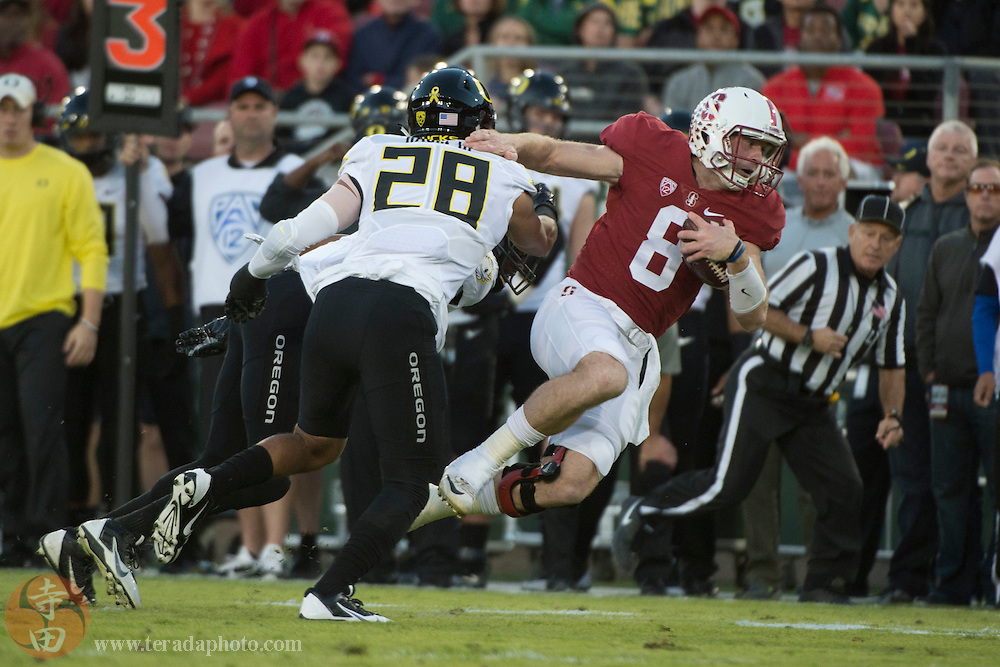 November 14, 2015; Stanford, CA, USA; Stanford Cardinal quarterback Kevin Hogan (8) is tackled by Oregon Ducks linebacker Johnny Ragin III (28) during the first quarter at Stanford Stadium.