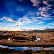 The autumn sun sets over the water lines of the Hayden Valley in Yellowstone National Park.