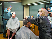15 MAY 2020 - DES MOINES, IOWA: RHONDA STEWART, right, and BRUCE FULTON, barbers in Ferg's Barbershop in downtown Des Moines, wear face masks while they cut customers' hair for the first time in two months Friday.  The Governor of Iowa allowed most businesses in Iowa to reopen today, including barbershops, restaurants, coffee shops and malls. Restaurants are supposed to be working at 50% of normal capacity and barbershops are urged to take reservations and not allow customers to wait in the shop. Barbers are urged to wear face masks. Movie theaters, bars, museums, zoos, and casinons are still closed. On Friday, 15 May, Iowa reported 14,049 cases of COVID-19 and 336 deaths from disease since the start of the pandemic. Iowa's total number of infections continue to rise and several communities in Iowa have emerged as national hotspots for the spread of Coronavirus (SARS-CoV-2).         PHOTO BY JACK KURTZ