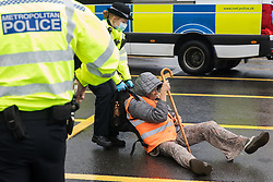 Colnbrook, UK. 27th September, 2021. A Metropolitan Police officer drags an Insulate Britain climate activist out of a M25 slip road at Junction 14 close to Heathrow airport which was blocked as part of a campaign intended to push the UK government to make significant legislative change to start lowering emissions. The activists are demanding that the government immediately promises both to fully fund and ensure the insulation of all social housing in Britain by 2025 and to produce within four months a legally binding national plan to fully fund and ensure the full low-energy and low-carbon whole-house retrofit, with no externalised costs, of all homes in Britain by 2030.