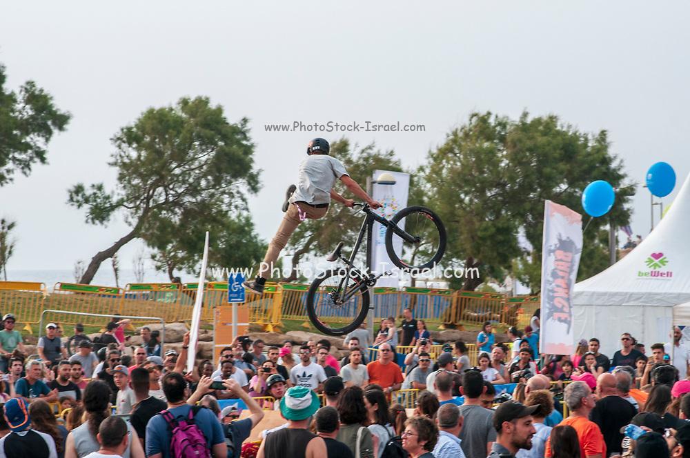 Bicycle stuntman a crowd of people watching below