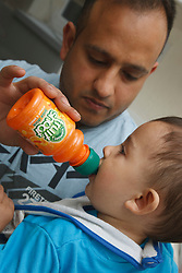 Father and son at home with fruit squash.