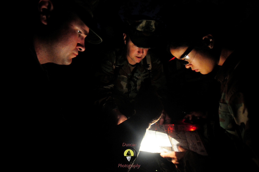 October 10, 2008 -- GULFPORT, Miss. U.S. Navy Information Technology Specialist Jamie Marshall, right, plots a point on a map at night with the help of Construction Electrician 1st Class Sean Dement, left, and Senior Chief Equipment Operator George Waldrop as part of a land navigation course at Expeditionary Combat Skills School (ECS).  .The ECS school is designed to build a basic level of battlefield competence for sailors from the Navy's newly formed Expeditionary Combat  Combat Command  (NECC) community. The students have a wide range of precision modern warfare skills. Because the Navy is supporting missions ashore more than ever, there is a significant need for sailors to gain land-based combat skills. The aim of the school is to provide NECC sailors basic warfighting and survival capabilities. Photo by Mass Communication Specialist 1st Class Roger S. Duncan.  (RELEASED)