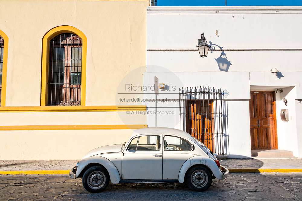 A white Volkswagen Beetle parked outside brightly painted Spanish colonial style buildings in the Barrio Antiguo or Spanish Quarter neighborhood adjacent to the Macroplaza Grand Plaza in Monterrey, Nuevo Leon, Mexico.
