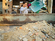 """14 FEBRUARY 2019 - SIHANOUKVILLE, CAMBODIA:  A Cambodian woman puts construction debris into the bed of a truck on the site of a Chinese hotel being built in Sihanoukville. There are about 80 Chinese casinos and resort hotels open in Sihanoukville and dozens more under construction. The casinos are changing the city, once a sleepy port on Southeast Asia's """"backpacker trail"""" into a booming city. The change is coming with a cost though. Many Cambodian residents of Sihanoukville  have lost their homes to make way for the casinos and the jobs are going to Chinese workers, brought in to build casinos and work in the casinos.    PHOTO BY JACK KURTZ"""