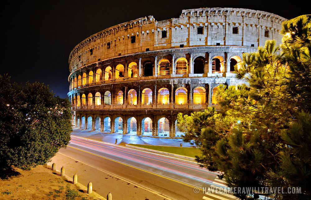 ROME, Italy - A shot of Rome's famous and historic Coliseum at night, with the lights of passing traffic blurred above the road.
