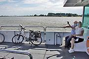 Nederland, Tiel, Wamel, 21-8-2020 Passagiers op het fietspontje van Tiel naar Wamel in het land van maas en waal . Ze dragen verplicht een mondkapje vanwege het coronabesmettingsgevaar . Een ouder echtpaar maakt een selfie met masker . Foto: ANP/ Hollandse Hoogte/ Flip Franssen