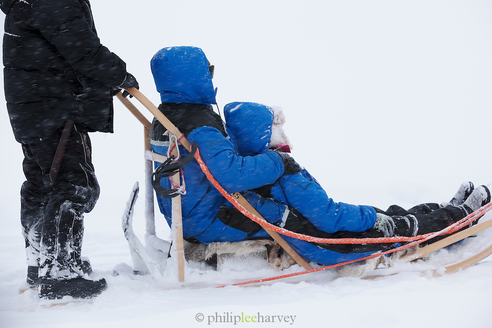 Tourists take a ride on a sledge pulled by huskies in Kirkeness, Finnmark region, northern Norway