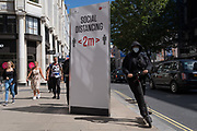 A man riding an eScooter speeds past a social distance post on Oxford Street during the Coronavirus pandemic, on 20th August 2020, in London, England