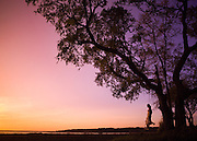 A young girl enjoys the sunset from her tree swing under a South Carolina Oak.