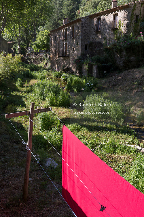 A pink sheet dries on a communal village washing line in morning sunlight, on 26th May, 2017, in Termes, Languedoc-Rousillon, south of France