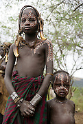 Africa, Ethiopia, Debub Omo Zone, children of the Mursi tribe. A nomadic cattle herder ethnic group located in Southern Ethiopia, close to the Sudanese border. Woman with clay lip disc as body ornaments