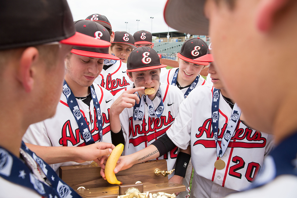 Papillion, Nebraska --<br /> <br /> Elkhorn's Connor Fowler holds his championship medal between his teeth while his teammate Logan Davis, No. 20, places a good luck charm, a fake banana, on their Class B state title trophy after defeating Omaha Skutt at Werner Park on Friday, May 20, 2016, in Papillion. Elkhorn defeated Omaha Skutt 4-3 in eight innings. During the season the team decided to use the fruit not as a snack but as a good luck charm. They later switched to the more durable, fake, produce.<br /> <br /> (MATT DIXON/THE WORLD-HERALD)