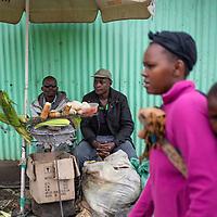 A street scene in Mukuru Kwa Njenga, Nairobi, a man sells roast sweetcorn from his stall.