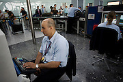 """Security employed by contractor OCS monitors an X-ray machine at Heathrow Airport's Terminal 5. Teams of 5-8 perform a rotational order of tasks, changing every 20 minutes: A loader (asking travellers to take off clothing, shoes etc); archway detectors; X-ray operator; liquid tester and bag searcher. The X-ray operator can earn a £50 bonus for a suspect item randomly inserted by undercover officials and known as an Airlock Find. Also, a Tip is a random image flashed on the screen that shows a suspect item they have to spot. A typical day of searched passengers is 25,000 passengers in T5. From writer Alain de Botton's book project """"A Week at the Airport: A Heathrow Diary"""" (2009). ."""