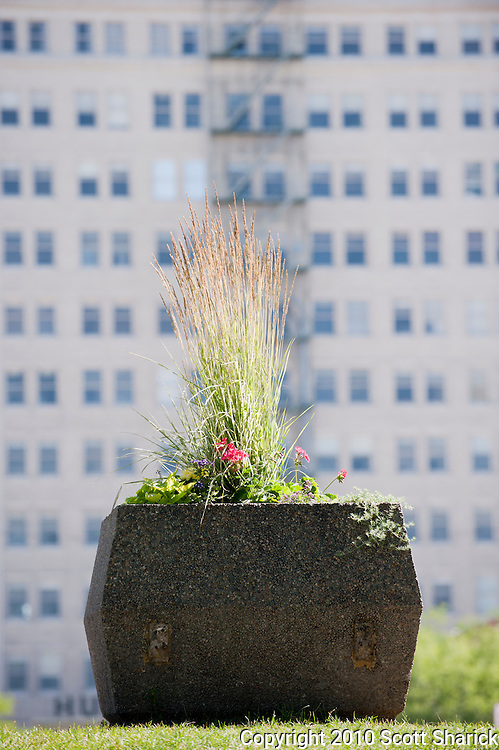 A large flower pot in front of a large apartment building in an urban setting. Missoula Photographer