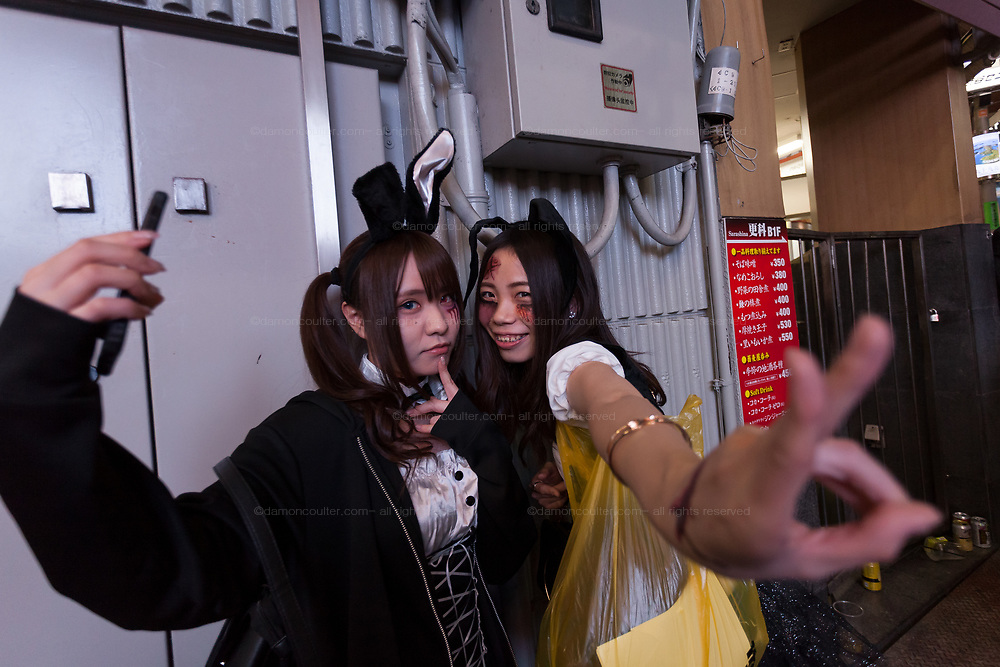 Two Japanese women in costume take a selfie during the Halloween celebrations Shibuya, Tokyo, Japan. Saturday October 27th 2018. The celebrations marking this event have grown in popularity in Japan recently. Enjoyed mostly by young adults who like to dress up, drink , dance and misbehave in parts of Tokyo like Shibuya and Roppongi. There has been a push back from Japanese society and the police to try to limit the bad behaviour.